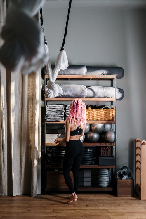 Woman in Black Leggings Standing Beside Brown Wooden Shelf