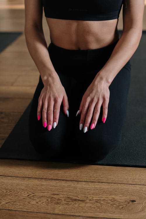 Woman in Black Tank Top and Black Leggings Sitting on Black Yoga Mat