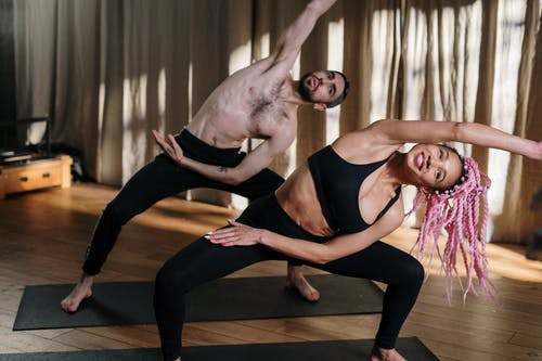 2 Women in Black Tank Top and Leggings Doing Yoga