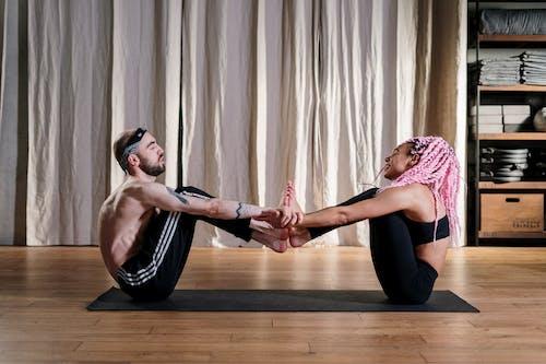 Woman in Pink Tank Top and Black Leggings Doing Yoga