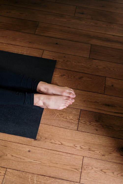 Person Standing on Black Area Rug