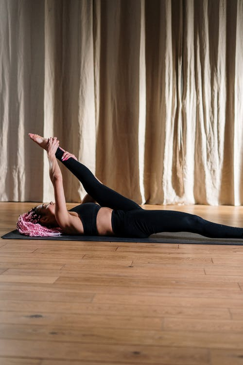 Woman in Black Tank Top and Black Leggings Lying on Pink Textile