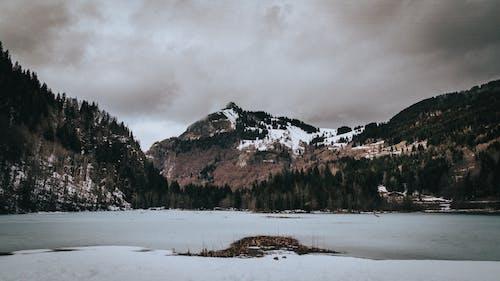 Snowy ridge under cloudy sky in wintertime