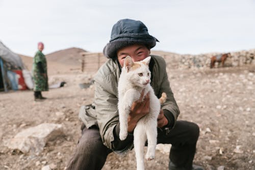 Cheerful Mongolian boy in hat squatting and holding cat near ger