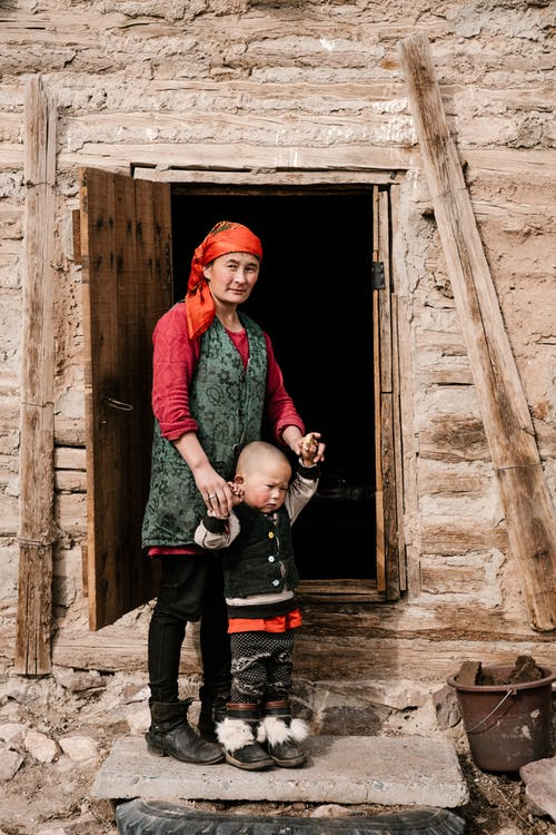 Mature ethnic female in headscarf looking at camera while standing at entrance of poor house holding hands of little boy