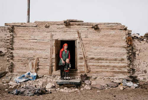 Ethnic woman and little boy standing near destroyed house