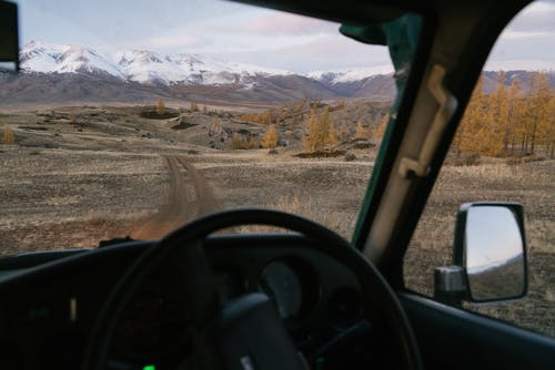 Empty road going through prairie to mountains viewed from car in countryside travel through Mongolia