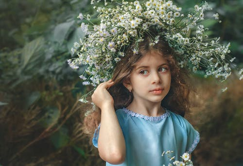 Thoughtful girl with chaplet standing near greenery