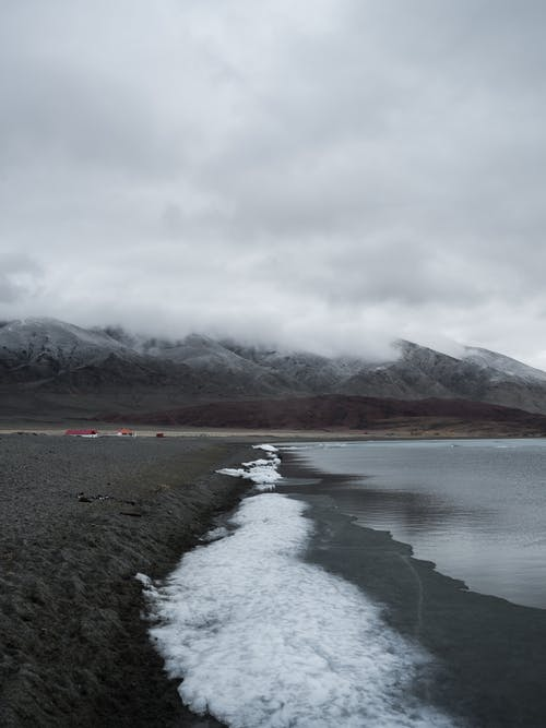 Picturesque landscape of frozen lake with snowy against calm mountain ridge in cloudy day