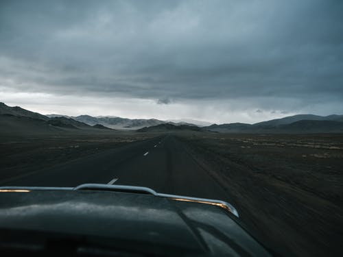 Asphalt road running away to remote mountains in haze and prairie seen from car in cloudy day