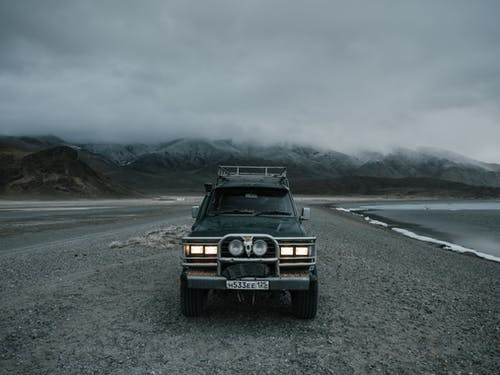 Car parked on seashore near mountains in foggy weather