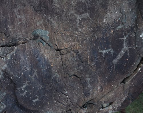 From above of dark gray natural slope with shabby surface and tiny aged paintings