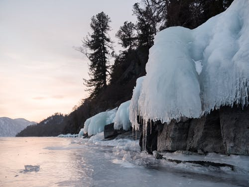 Icicles on hillside near frozen lake under cloudy sky