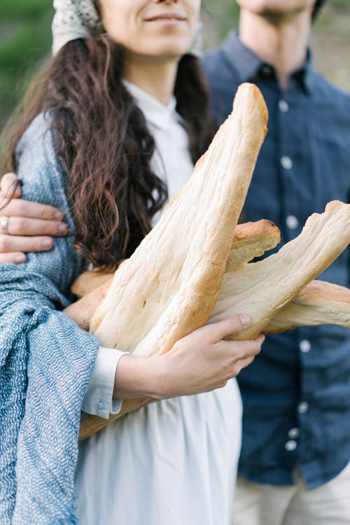 Crop couple carrying loaf of fresh bread