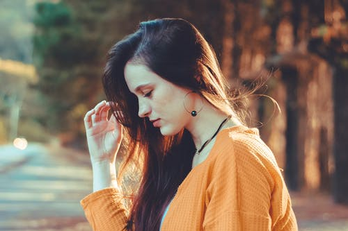 Side view tranquil pensive female in casual yellow sweater spending time in park and touching hair playfully