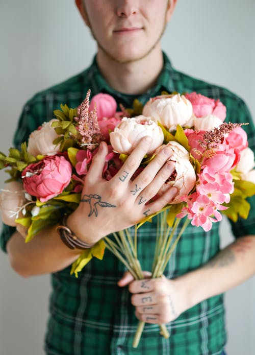Crop anonymous young tattooed male florist in checkered shirt smiling while holding bunch of fresh peonies against gray background