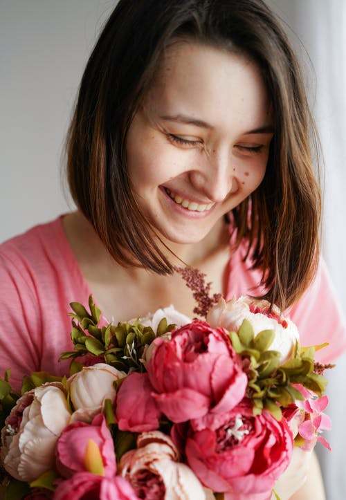 Smiling young woman with bunch of pink flowers