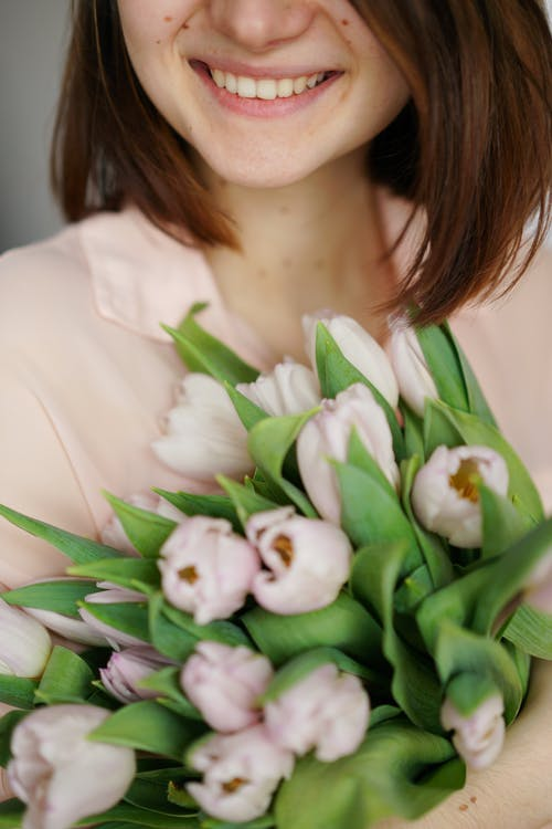 Crop smiling lady with tulip flowers