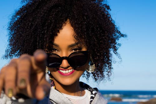 Crop happy young African American female with bright makeup and curly hair in stylish sunglasses standing on seashore and pointing finger at camera