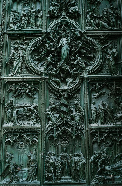 Magnificent details of green bronze door of medieval cathedral church with carved bas reliefs with biblical motives