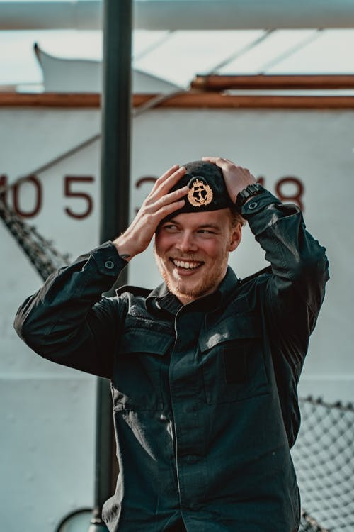 Cheerful military man putting on service cap