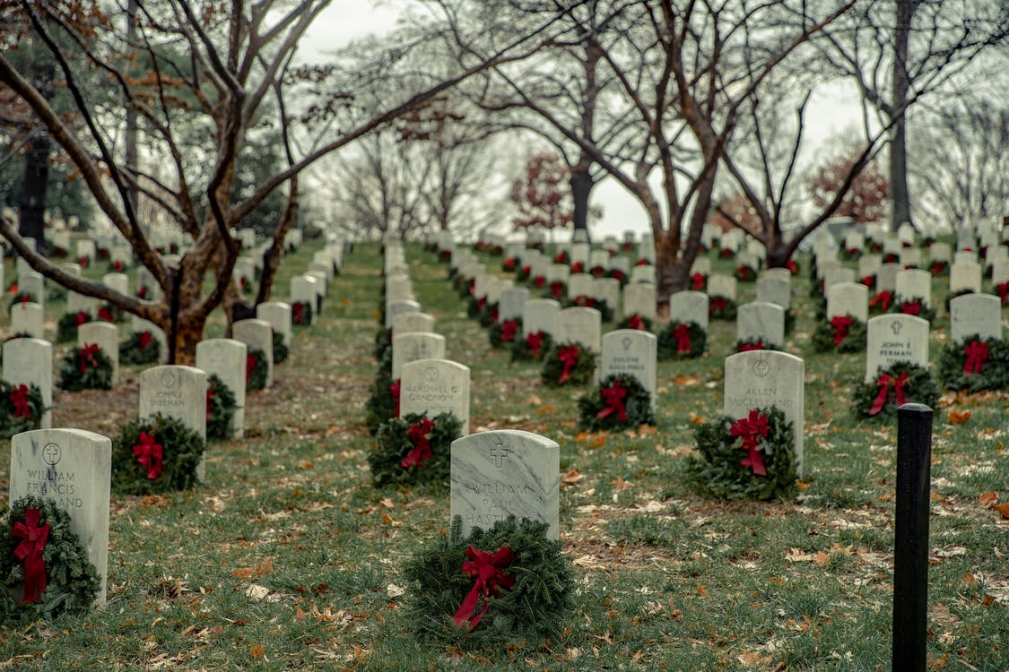 Perspective view of military cemetery with rows of similar headstones with wreaths under leafless trees on autumn day