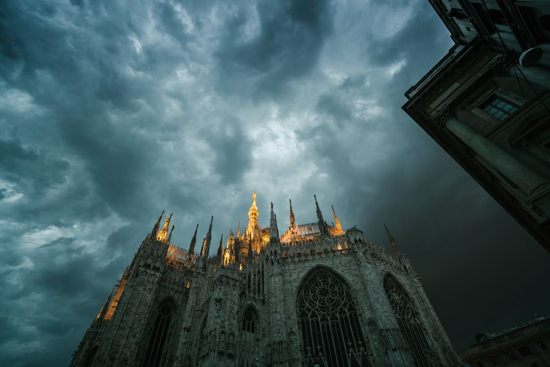 Low angle of Metropolitan Cathedral Basilica of Nativity of Saint Mary in Milan with sharp spires lit up with bright light against gloomy overcast sky
