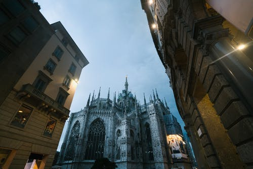 Low angle of city buildings and Milan Cathedral of Nativity of Saint Mary with glowing facade advertising on cloudy dusky evening