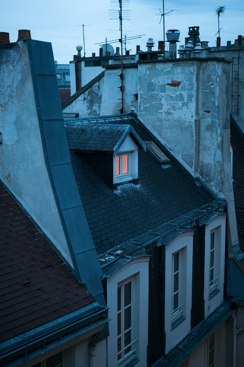 Old fashioned rooftop and windows of shabby building in European city on quiet dusky evening