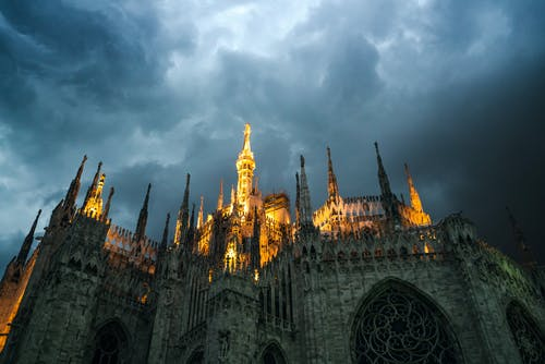 Milan Cathedral with glowing sharp spires under overcast sky