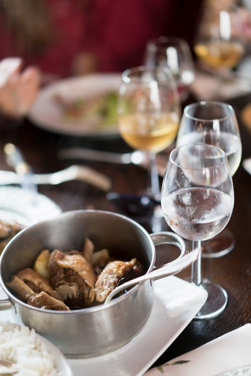 Saucepan with meat on white platter and glasses of white wine on restaurant table with blurred person having dinner in background