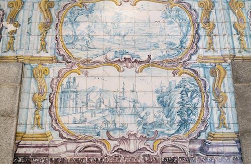 Amazing Azulejo tin glazed ceramic tilework depicting pastoral scene and ship in port on wall of building in Porto city in Portugal