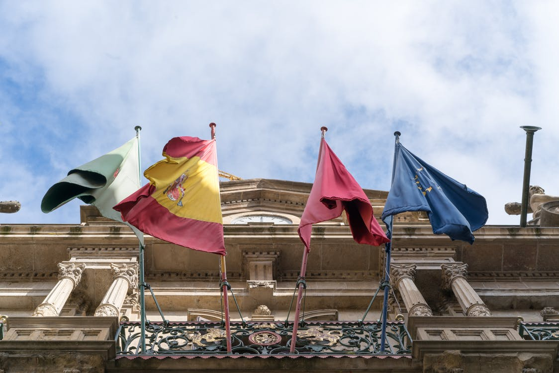 Flags waving on old ornate city building on fine day