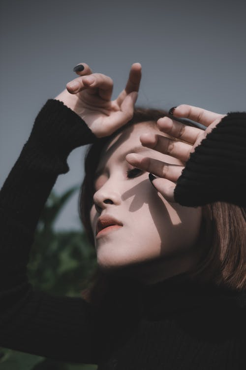 Tranquil serene female in black turtleneck standing with eyes closed in park and holding hands near face