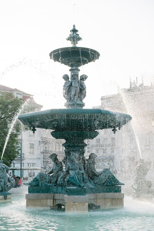 Bronze fountain on Rossio Square in Lisbon on fine day