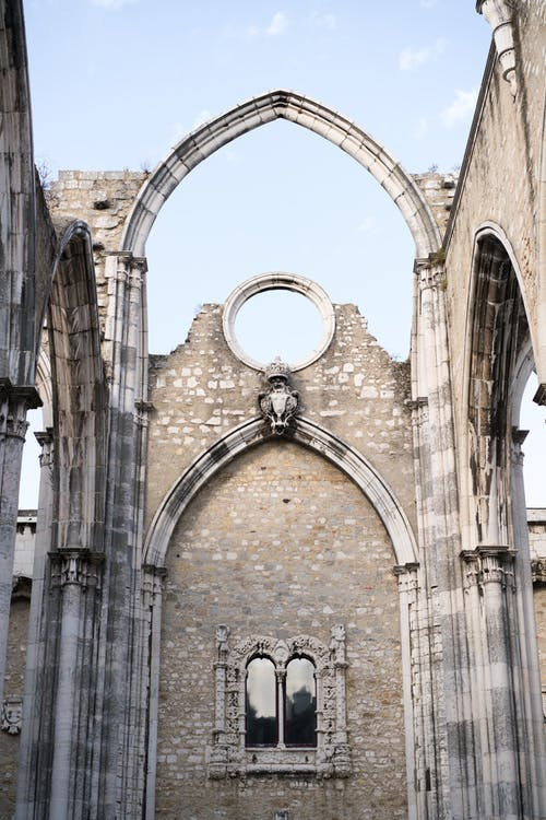 Part of Carmo Convent with pointed arch under blue sky