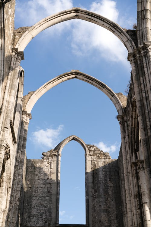 Old arches of Carmo Convent in Lisbon against blue sky