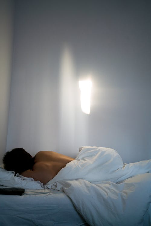 Unrecognizable person with bare back sleeping in bed