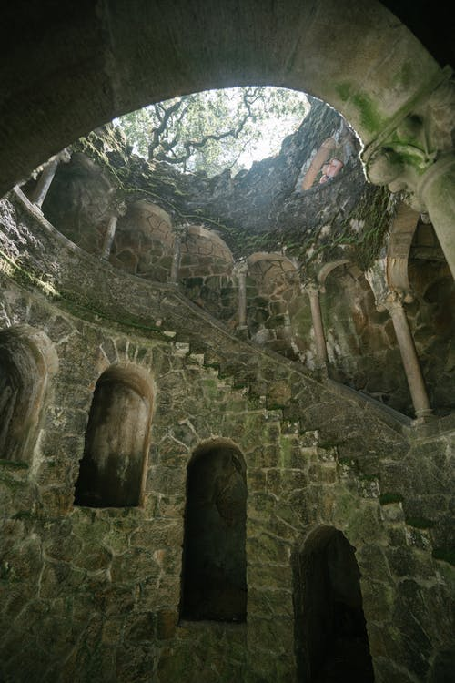From below of dimly lit Initiation Well with spiral stairway and walls grown with moss at Quinta da Regaleira in Portugal