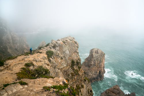Back view of unrecognizable tourist in outerwear standing on majestic rocky cliff above sea