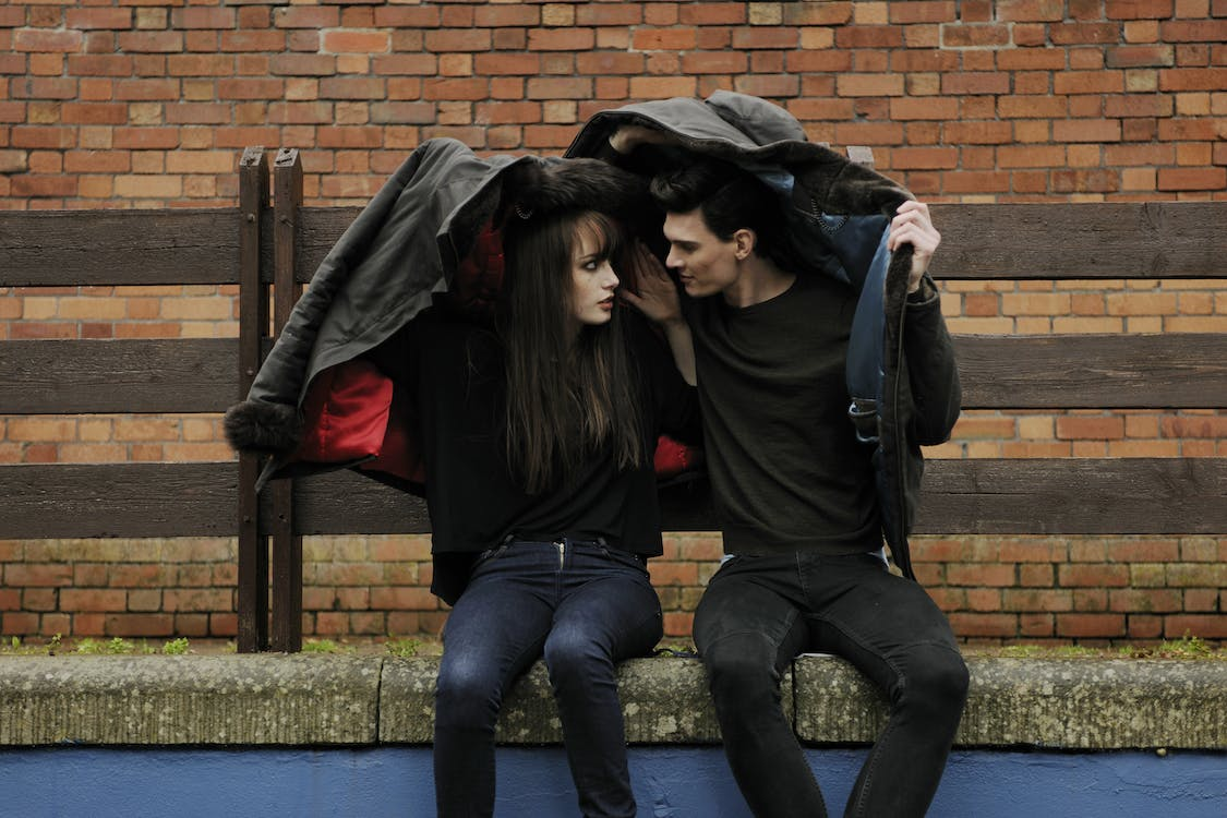 Man and Woman Sitting on Bench While Covering Heads With Jackets