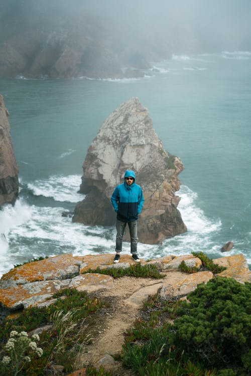 Unrecognizable man standing on cliff above sea