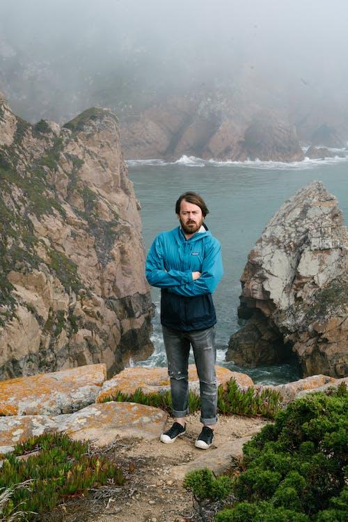 Traveler standing on stony place near sea