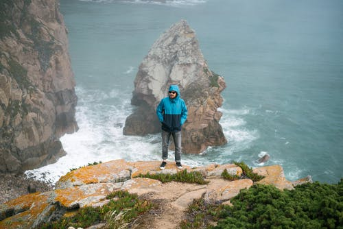 Unrecognizable man standing on edge of cliff