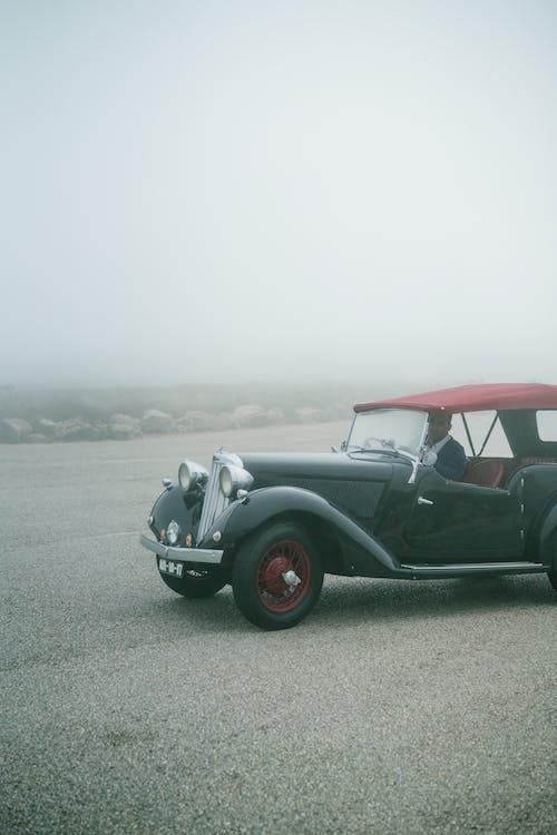 Unrecognizable man driving on retro fashioned car through fog on empty asphalt road