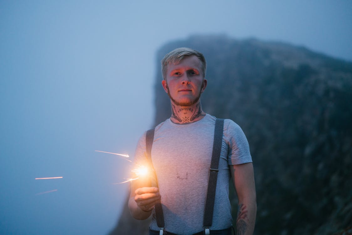 Serious tattooed male in casual wear standing with torch in hand on hill in evening time and looking at camera