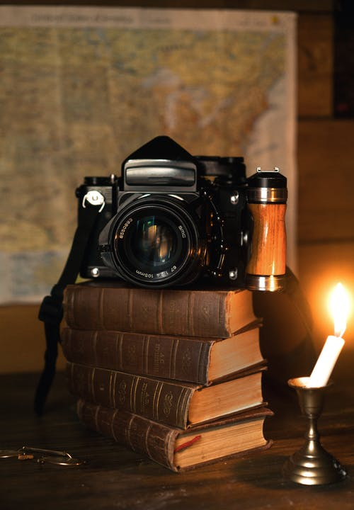 Vintage camera on old books near candle