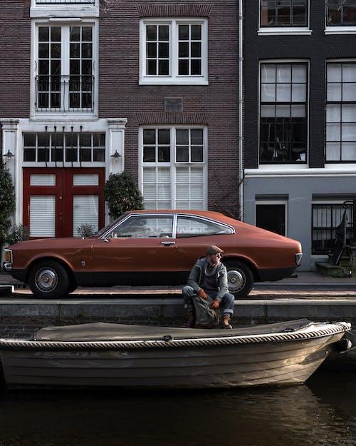 Man sitting near retro car on old street near canal