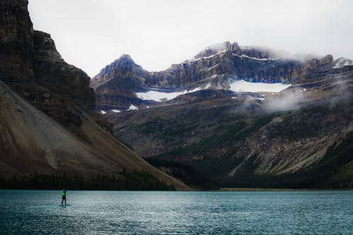 Distant tourist standing on surfboard on lake surface against majestic mountains with rough snowy peaks