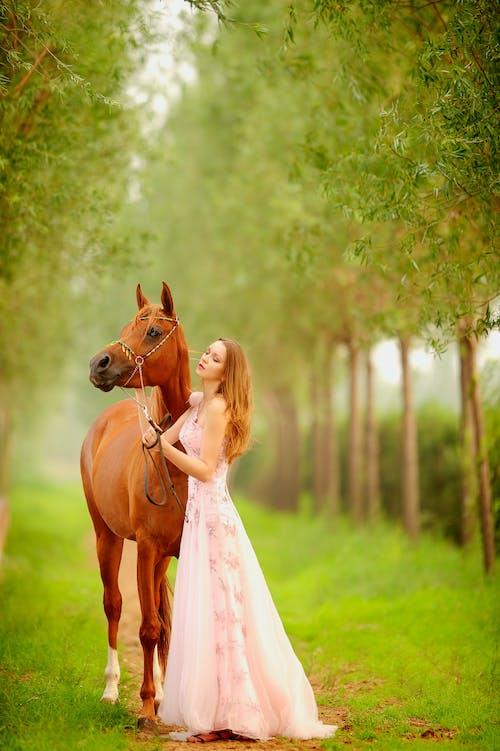 Gorgeous woman near brown horse in garden